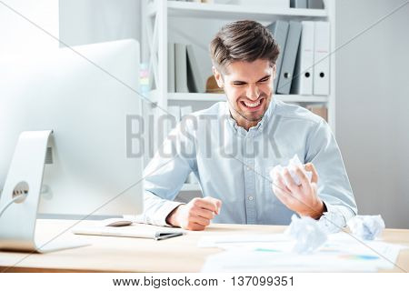 Mad annoyed young businessman working and crumpling paper in office