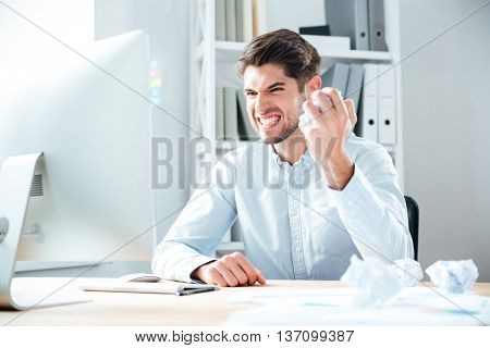 Angry crazy young businessman sitting and crumpling paper on his workplace