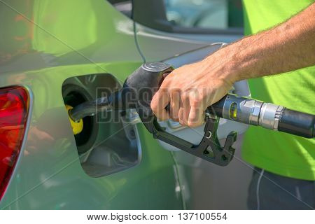 Pumping gas at gas station. Close up of a hand holding fuel nozzle.