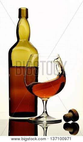 Open bottle and a glass of wine isolated on a white background