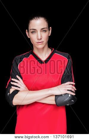 Female athlete posing with elbow pad on black background