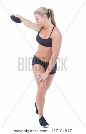 Female athlete throwing discus on white background