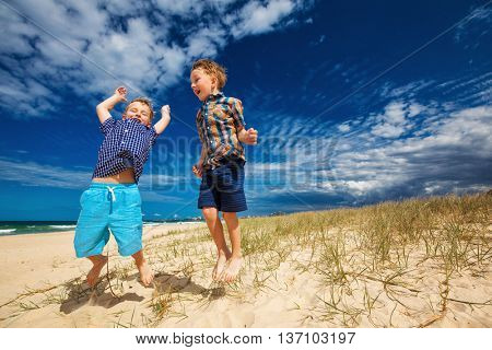 Young happy boys having fun on tropical beach, jumping up into the air
