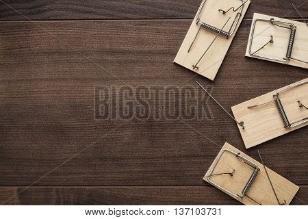 some mousetraps on the brown wooden background