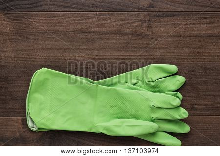 green rubber cleaning gloves on wooden background