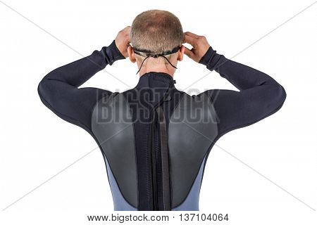 Rear view of swimmer in wetsuit wearing swimming goggles on white background