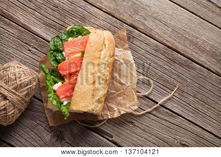 Sandwich with ciabatta bread, salmon, cheese and romaine salad on wooden table. Top view with copy space