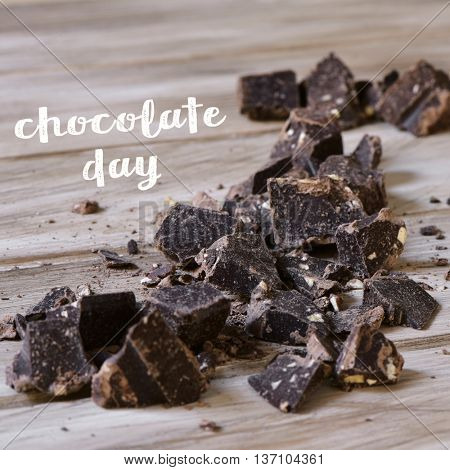 the text chocolate day and some pieces of dark chocolate on a rustic wooden surface