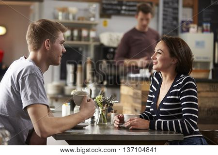 Adult couple talking at a table in a coffee shop, side view