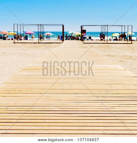 wooden boardwalk at the San Antonio Beach in Cullera, Spain, with the Mediterranean sea and unrecognizable sunbathers in the background