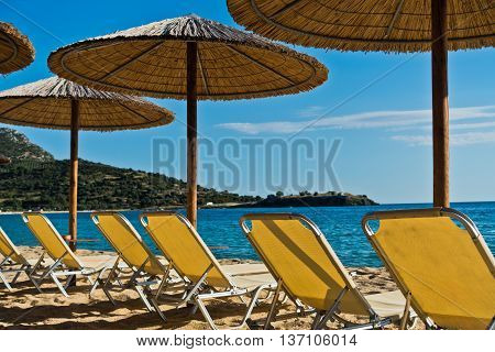Straw parasols on a beach with ruins of old roman fortress in background, Sithonia, Greece