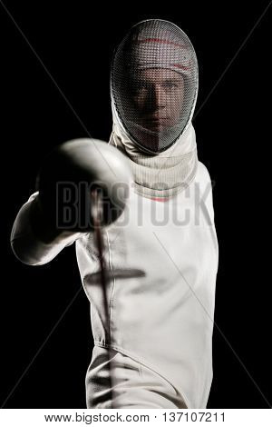 Portrait of man wearing fencing suit practicing with sword on black background