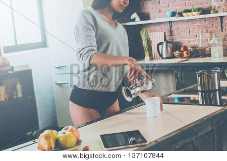 Pouring some fresh coffee. Close-up of attractive young mixed race woman pouring coffee to cup while standing in kitchen at home