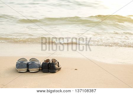 Father's shoes and son's shoes on thes beach with copy spacevintage filter