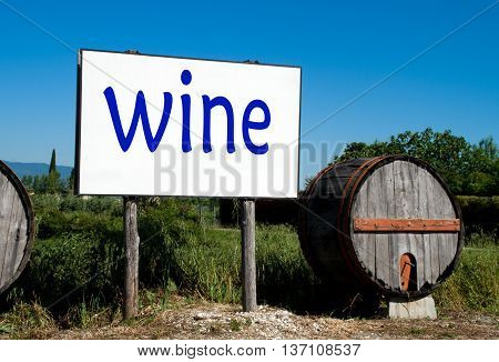 billboard in the countryside cultivated with traditional wooden barrel for wine sales