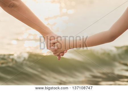 Hands of mother and daughter holding each other on sea background
