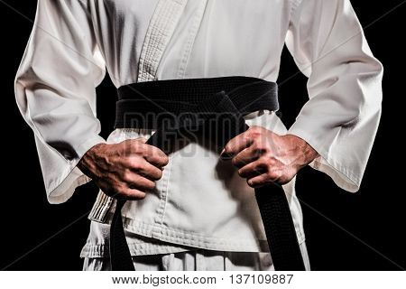 Fighter tightening karate belt on black background