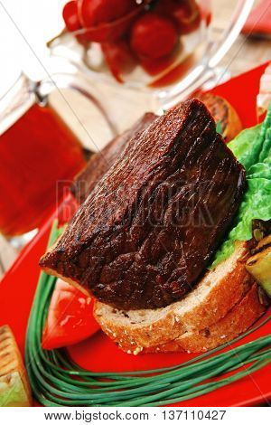 savory food : roast beef garnished with vegetables , juice and olives on red plate over wooden table