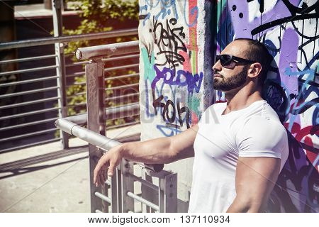 Handsome Muscular Hunk Man Outdoor in City Setting. Showing Healthy Body While Looking at Camera, Leaning against Graffiti Wall