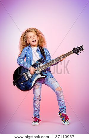 Modern seven year old girl with her electric guitar over pink background. Music concept.