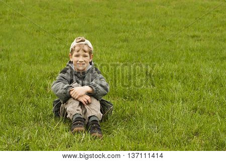 The nine-year-old boy sitting on a grass looks forward and smiles