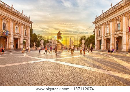 Rome, Italy - June 18, 2016: People walkin in Campidoglio square with statue on the Capitoline Hill, Mons Capitolinus, one of the seven hills of Rome.Designen by artist Michelangelo in Renaissance age