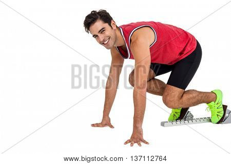 Happy male athlete in ready to run position on white background