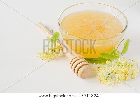 Natural linden honey in a transparent bowl and linden blossom on a white wooden background. Alternative medicine concept.