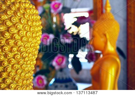 Close up Buddha face of a golden statue in the Wat Chalong temple Phuket Thailand.