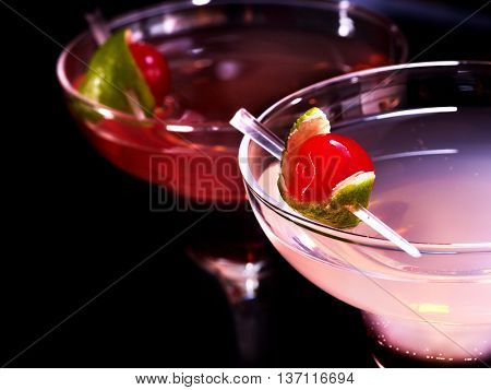 Part of alcohol cocktail in glass .Two pomegranate cocktail glasses with cherry on black background. Cocktail card.