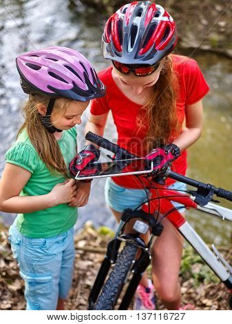 Bikes cycling girls. Girls children with tablet PC rides bicycle and searching way into internet map. Girl cycling fording throught water . Bicyclist is looking throught river.