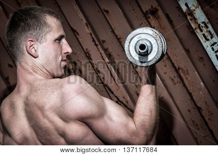 Young athletic man doing workout with heavy dumbbell