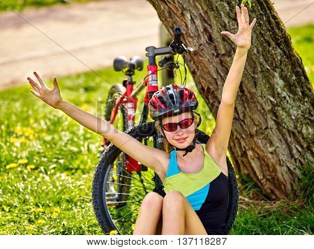 Bikes cycling girl. Girl rides bicycle. Girl in cycling sitting near bicycle and hand up. Cycling is good for health and mood. Cyclist looking into distance.