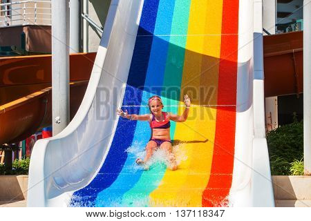 Child little girl on water slide at aquapark show hands up. There are some water slides with flowing water in aqua park. Summer water park holiday. Outdoor.