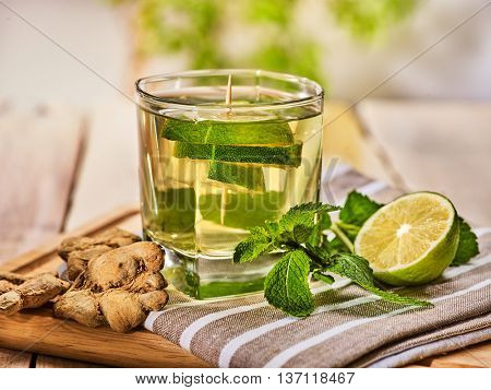 Healthy detox drink with ginger . On wooden boards glass with lime green tea and mint. A mint ginger drink number twenty seven with half and slice lime and napkin. Country life. Light background.