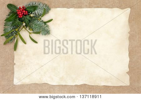 Old fashioned christmas abstract background  border with flora of holly, ivy, mistletoe and snow covered fir on parchment over hemp paper with copy space.