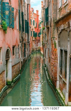 Colorful narrow lateral canal in Venice with docked boat, Italy