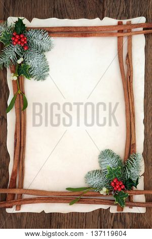 Christmas abstract background border with cinnamon sticks, holly, ivy, mistletoe and snow covered fir on parchment paper over oak wood.