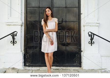 Beautiful woman standing at the black door of the castle, Gothic church door. girl in a pink dress, posing close up, resting, fashion lifestyle, long hair, tanned skin. Outdoors enjoying.