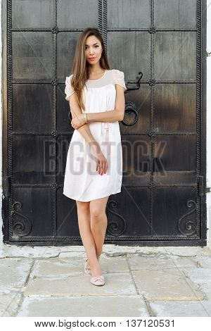 Beautiful woman standing at the black door of the castle, Gothic church door. girl in a pink dress, posing close up, resting, fashion lifestyle, long hair, tanned skin.