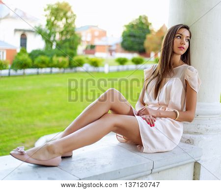 Beautiful brunette girl resting in the open air sitting, dreaming of looking into the distance, business woman with long hair. Fashion lifestyle, glamorous life, the student after graduation.