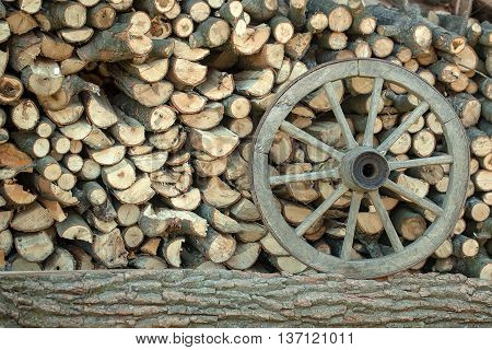 Pile of chopped wood with a wooden wheel