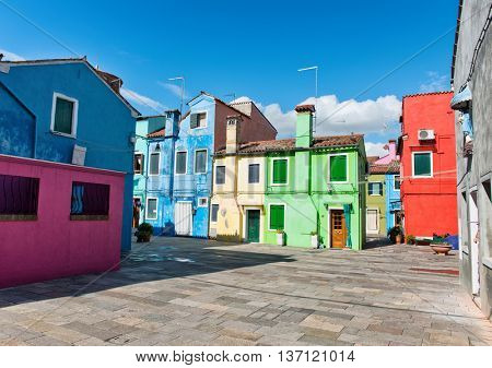 Square in Burano, Venice lined with colorful houses painted in bright colors to guide the fishermen home in fog