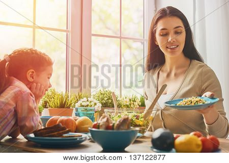 Happy family having dinner together sitting at the rustic wooden table. Mother and her daughter enjoying family dinner together.