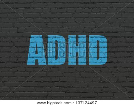 Health concept: Painted blue text ADHD on Black Brick wall background