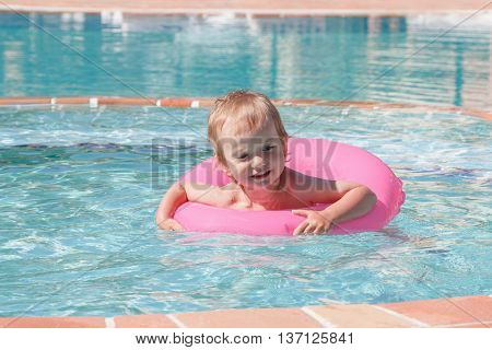 Little boy playing in the pool on a summer's day holiday