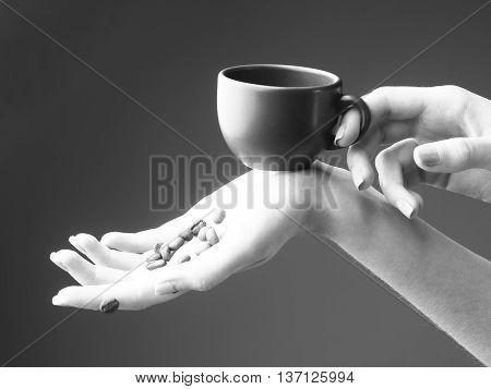 female hands with soft tender skin and manicure holding fresh or fried aroma coffee beans and cup on studio background black and white
