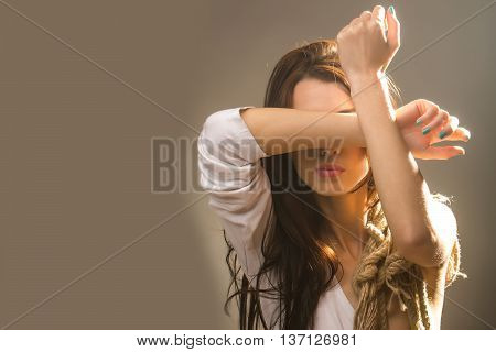 young pretty woman with rope on raised hands in white shirt has long brunette hair standing on grey backgound copy space