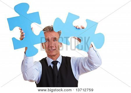Business Man Solving Oversized Jigsaw Puzzle