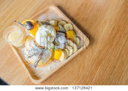 Pancake and fruit with ice cream on table